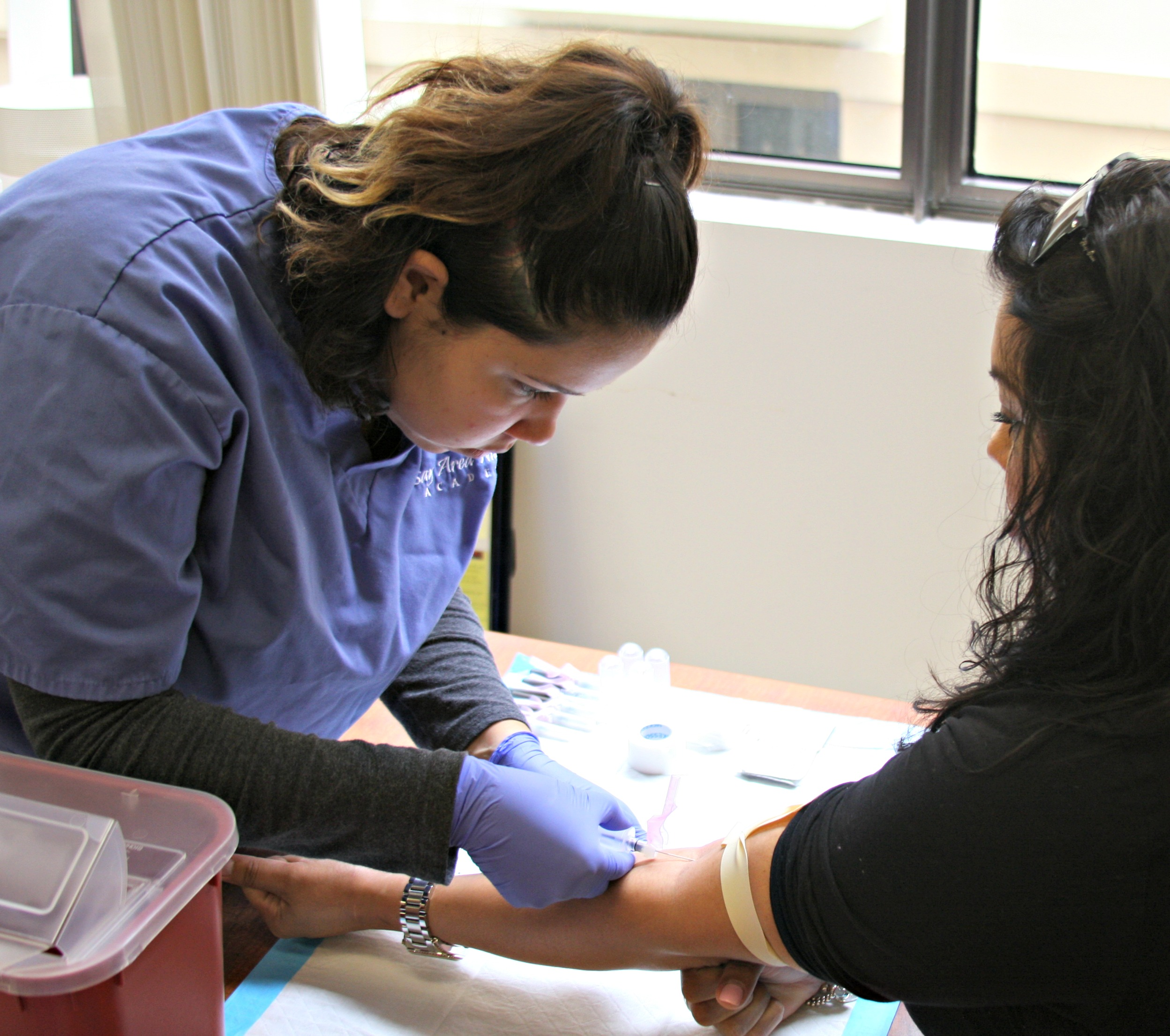 A Medical Assistant student learning phlebotomy